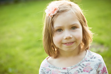 Portrait of a smiling little girl outdoors. Close-up