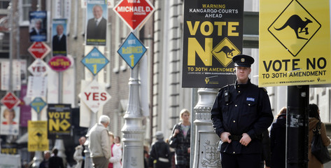 A member of the Gardai stands under election placards adorning lamp posts along Merrion Square on polling day in central Dublin