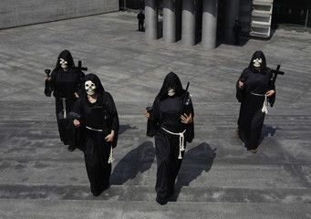 People in skull masks walk near an altar assembled in homage of people who died of diabetes and obesity in Mexico City