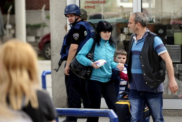 Man and his family leave the conflict area near a police checkpoint in Kumanovo