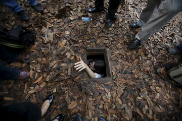 A French journalist tries to disappear into the Cu Chi tunnel network through a hole camouflaged on the jungle floor during a guided tour near Ho Chi Minh City