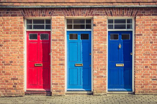 Three differently coloured front doors at the entrance of old English terraced houses. Canterbury, England.