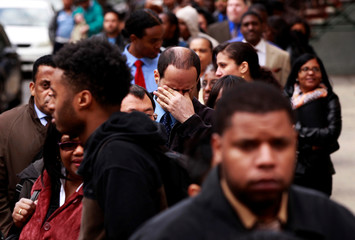 Man rubs his eyes as he waits in a line of jobseekers, to attend the Dr. Martin Luther King Jr. career fair held by the New York State department of Labor in New York