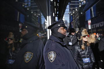 A New York Police officer watches fans at the Super Bowl Boulevard fan zone ahead of Super Bowl XLVIII in New York
