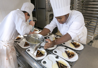 Students prepare plates with chocolate cake as they attend a pastry class at the Institut Paul Bocuse, in a 19th century chateau, in Ecully near Lyon