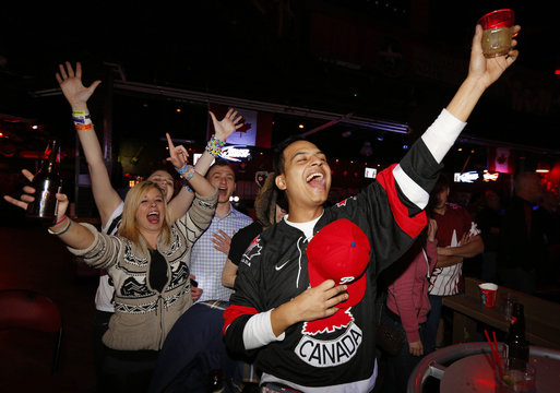 Team Canada hockey fans celebrate their team's win against Team USA at the men's ice hockey semi-final game at the Sochi 2014 Winter Olympic Games, while watching a televised broadcast of the game at Cowboys Bar in Calgary.