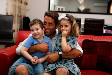 Noah and Lahela al-Amin pose for a picture with their father Ali Zeid al-Amin in their family home in Beirut, Lebanon