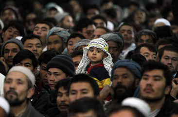 Afghans listen to Afghan President Hamid Karzai speak at a mosque during an Ashura procession in Kabul