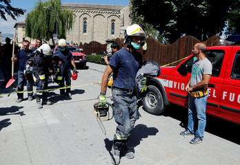 Firefighters of Vatican City leave the damaged areas following an earthquake in Amatrice