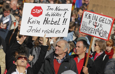 A woman holds up a placard during demonstration against financial injustices in Frankfurt