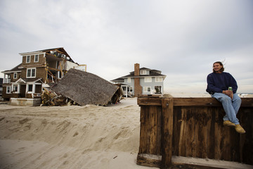 Resident Pete Gilman sits on a wooden breakwater in front of a home heavily damaged by the storm surge of superstorm Sandy in the town of Mantoloking
