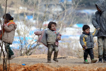 Internally displaced children, covered with mud, wait with their families as they are stuck in the town of Khirbet Al-Joz, in Latakia countryside, waiting to get permission to cross into Turkey near the Syrian-Turkish border