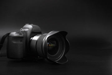 camera with lens on a black background. Canon is the world's largest SLR camera manufacturer.