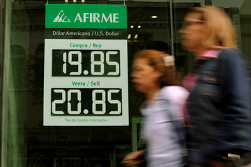 Women walk past a board displaying the exchange rate of Mexican peso against the U.S. dollar at an Afirme bank branch in Monterrey