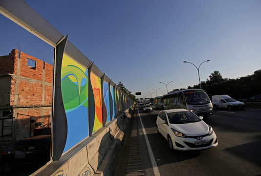 Banners advertising the 2016 Rio Olympics are pictured near the Mare slums complex of the Linha Vermelha freeway connecting Rio de Janeiro's International Airport with Rio de Janeiro's downtown and south zone