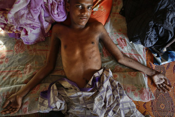 Akram, an 18-year-old Rohingya, who cannot walk and whose body is pocked with fly-blown sores from months of immobility, rests on a makeshift bed at a mosque near Songkhla