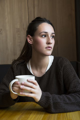 Portrait of serious woman with cup of coffee in a coffee shop