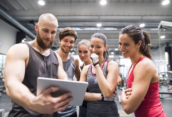 Group of happy athletes with tablet after exercising in gym