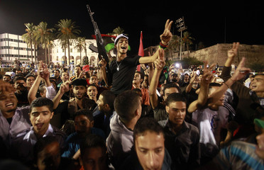 Libyans celebrate after hearing the capture of Muammar Gaddafi's son Mo'tassim, at Martyrs square in Tripoli