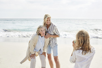 Little girl taking pictures on the beach of her mother and grandmother