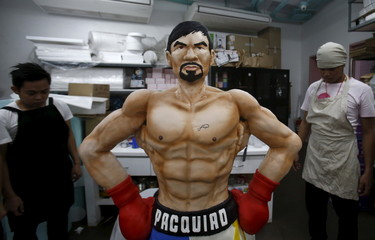 Workers from a bakery show a life-size 70-kg chocolate cake of local boxing icon Manny Pacquiao to the media in Manila