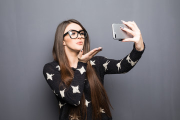 Young pretty girl making a selfie and sending a kiss on gray background