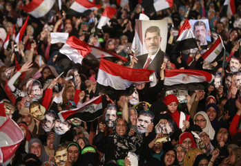 Members of the Muslim Brotherhood and supporters of deposed Egyptian President Mursi hold his pictures as they wave Egyptian flags and wear masks of him while gathering at Rabaa Adawiya square, in Cairo