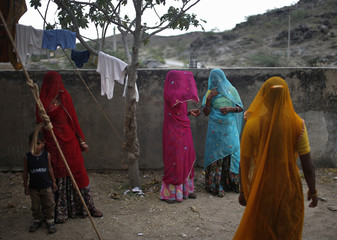 Women chat as they leave a polling station after casting their votes in Ajmer district