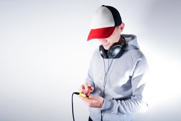 Man in a gray hoodie on a white background listening music from a smartphone in a big headset