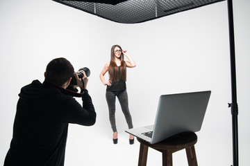 Girl the photographer takes pictures of model in black on a white background