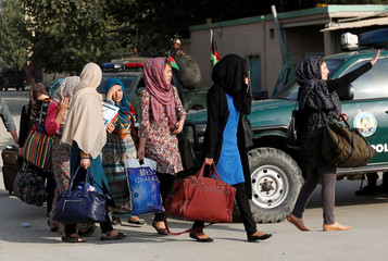 Students walk toward a police vehicle after they were rescued from the site of an attack at the American University of Afghanistan in Kabul