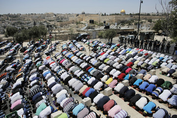 The Dome of the Rock is seen in the background as Palestinians pray on the first Friday of Ramadan in Ras al-Amud