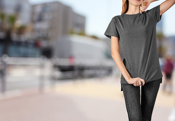Young woman in blank grey t-shirt standing against textured wall, close up