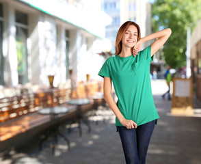 Young woman in blank green t-shirt standing against brick wall