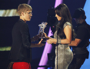 "Bieber accepts his best male video award  for ""U Smile"" from Kardashian at the 2011 MTV Video Music Awards in Los Angeles"