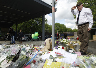 Former soldier Scott Perry salutes over flowers left outside an army barracks near the scene of a killing in Woolwich