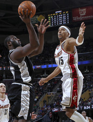 San Antonio Spurs' DeJuan Blair puts up a shot as Cleveland Cavaliers' Jamario Moon attempts to make a block during the fourth quarter of their NBA basketball game in Cleveland