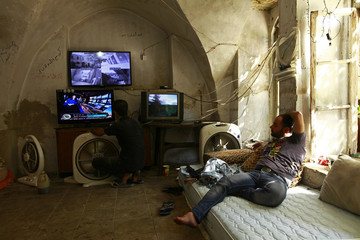 Free Syrian Army fighters watch surveillance footage from cameras they installed on the front line, at a safe house in Aleppo