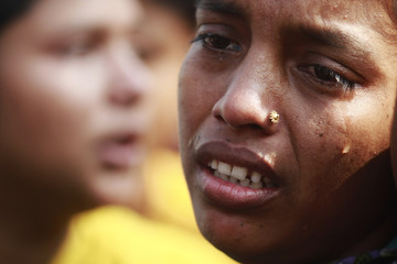 A worker cries during a protest against the death of her colleagues after a devastating fire in a garment factory which killed more than 100 people, in Savar