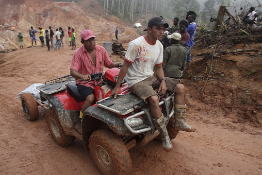 Brazilian rescue workers transport the body of one of seven wildcat miners who died in a gold mine collapse at Money Hill