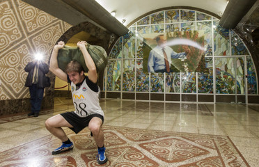 A participant performs squats exercise with load in front of a picture of Kazakh President Nazarbayev during a competition at underground metro station in Almaty