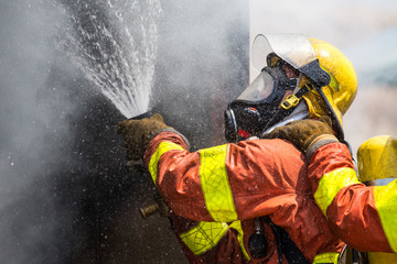 firefighter water spray by high pressure fire hose in smoke and droplets