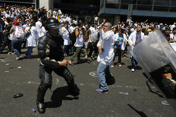 A national policeman scuffles with an anti-government doctor during a march demanding medical supplies for hospitals in Caracas