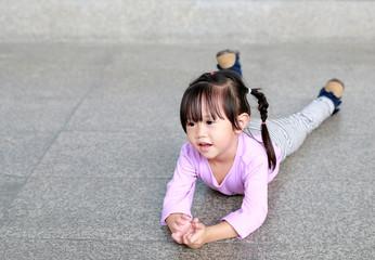 Portrait of happy cute little girl lying on floor corridor.