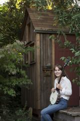 Woman holding banjo outdoors