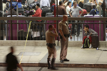 A man sits with his luggage next to officers manning a police line after a shooting at the Los Angeles International Airport