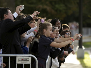 People take photos of Pope Francis leaving Vatican Embassy for U.S. Capitol in Washington