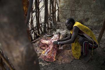 A man butchers a cow in Pibor, South Sudan