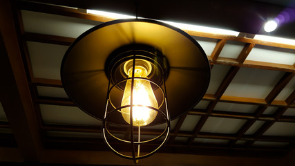 Old dusty light bulb glowing in the dark