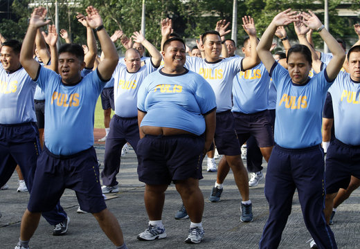 Policemen warm up before exercise during Weight Loss Management Program in Manila